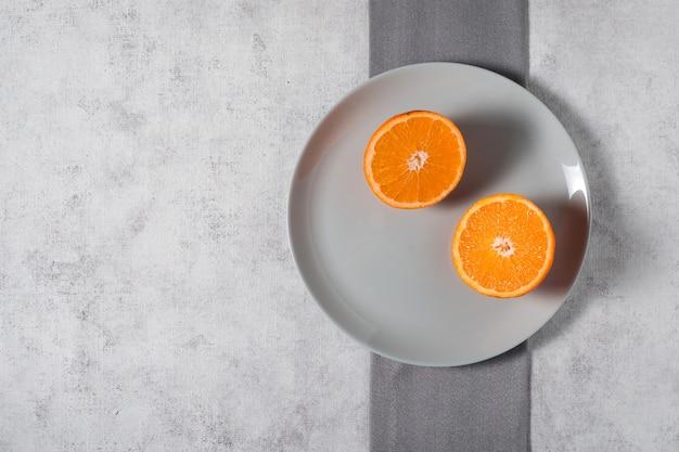 Вид сверху на нарезанный апельсин на тарелке