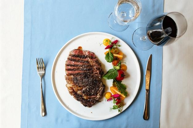 青いテーブルの上に新鮮な野菜のサラダとスライスしたリブアイビーフステーキの上面図