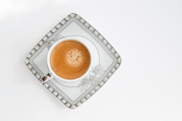 Вид сверху на маленькую кофейную чашку, наполненную эспрессо, на квадратной тарелке на белой поверхности