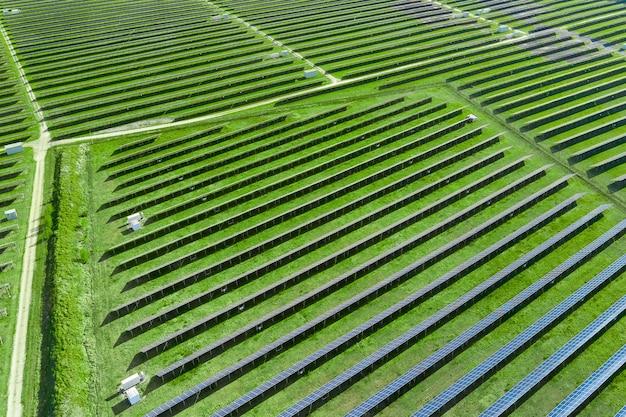 Вид сверху на панели солнечных батарей в поле с зеленой травой.