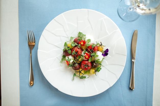 Вид сверху на салат из очищенных помидоров с зеленью на синем сервированном столе