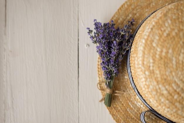 Вид сверху на соломенную шляпу - милый букет оливковой лаванды. сухая трава. вид сверху