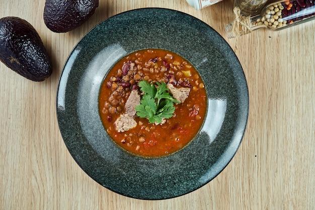 Взгляд сверху на вкусном carne жулика chili или chili с мясом, пряным тушёным мясом содержа перцы chili, мясо, фасоли, томат. традиционная кухня южного техаса.