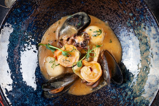Вид сверху на вкусные обжаренные морепродукты в сливочном соусе подается в темной посуде. креветки, морские гребешки, мидии, осьминог в темной тарелке. закройте копировать пространство здоровая пища