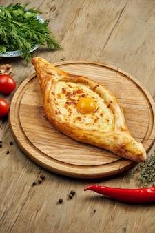 Вид сверху на вкусный традиционный аджарский хачапури - открытый запеченный пирог с сыром (сулугуни) и яичным желтком на деревянном подносе. традиционная грузинская еда