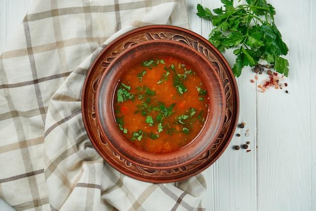 Взгляд сверху на вкусном, традиционном супе kharcho с говядиной, рисом, пюре сливы вишни и прерванными грецкими орехами в керамическом шаре на деревянной предпосылке. вкусная грузинская кухня