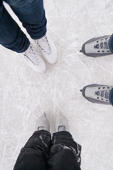 얼음 위에서 평상복을 입고 스케이트를 입은 엄마 아빠와 아들의 상위 뷰