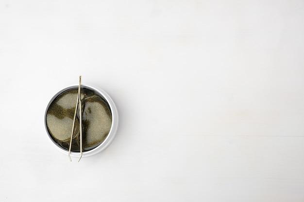 Вид сверху на банку с золотыми коллагеновыми гидрогелевыми пластырями для глаз