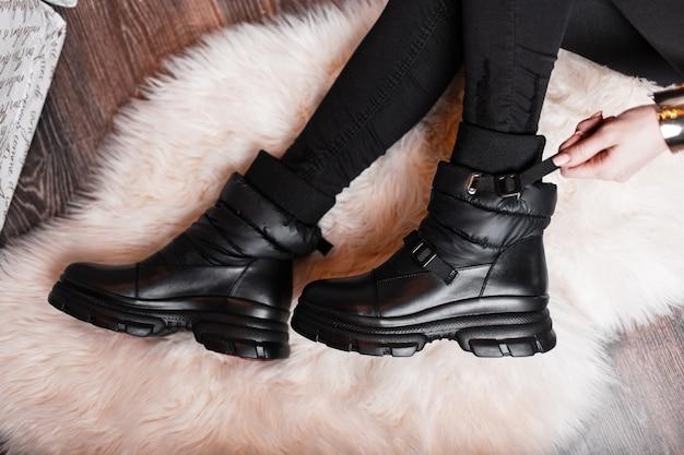 Вид сверху на ноги молодой женщины в модных кожаных туфлях в стильных черных джинсах в студии
