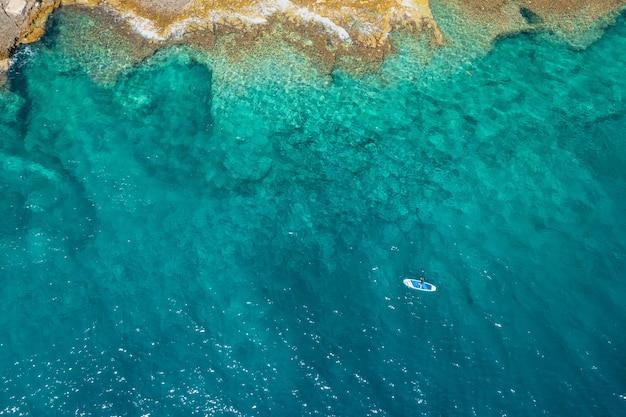 岩と澄んだターコイズブルーの水で海のスタンドアップパドルボードsupの男の上面図
