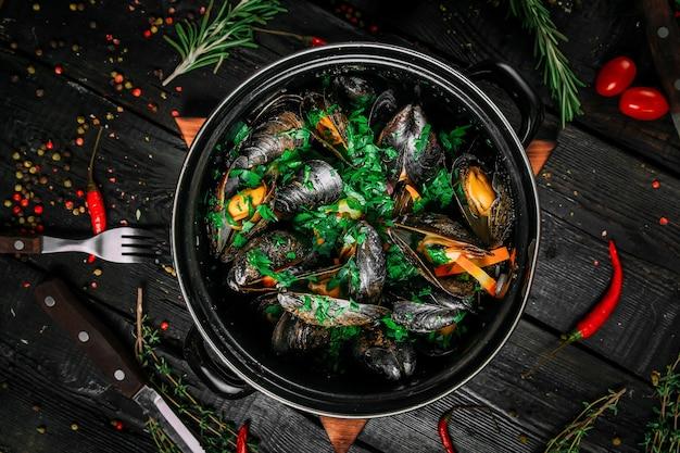 Вид сверху на мидии в сливочном соусе с петрушкой в большом черном ведре на черном деревянном фоне, горизонтальный