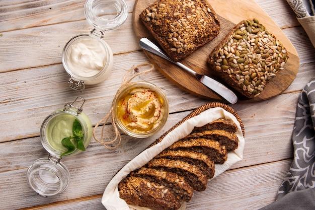 Вид сверху на три разных соуса в стеклянных банках с нарезанным цельнозерновым хлебом на деревянных досках