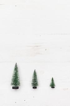 白い木製の背景の上の3つの小さなクリスマスツリーの上面図。休日と冬のコンセプト。