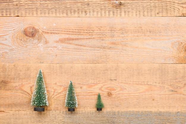 木製の背景に3つの小さなクリスマスツリーの上面図