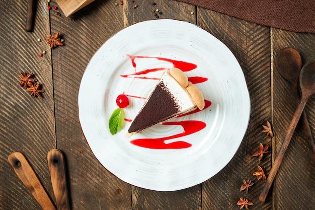 木製のテーブルにベリーソースをかけたティラミスケーキの上面図
