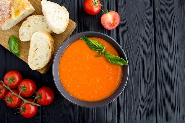 Вид сверху на томатный суп в темной миске