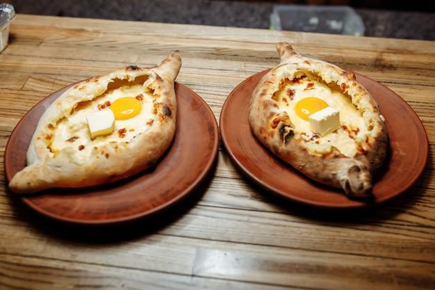 伝統的なadjarian khachapuri-木製のトレイに溶けた塩チーズスルグニと卵の黄身を開いた焼きたてのパイの平面図。伝統的なグルジア料理