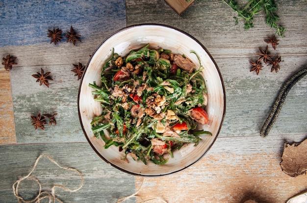 Вид сверху на салат из тунца с рукколой в бальзамической заправке и грецкими орехами