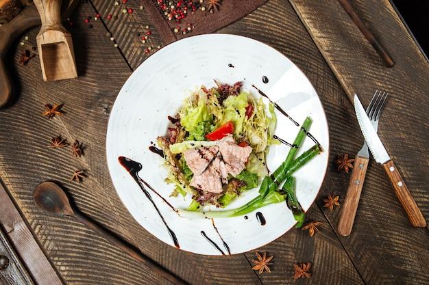 Вид сверху на салат из тунца со свежей зеленью салата на деревянном столе