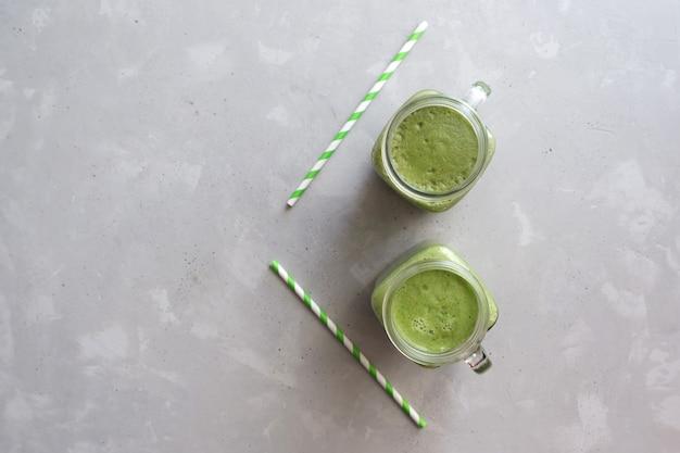 灰色のコンクリートに緑のスムージーと緑の尿細管を2杯の平面図