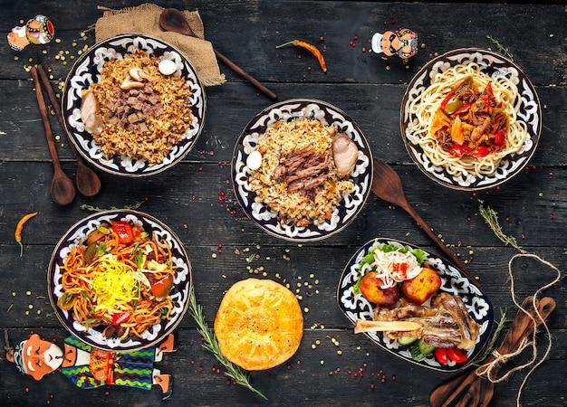 Вид сверху на блюда узбекской восточной кухни на деревянной поверхности