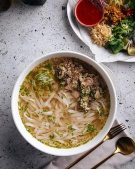 Вид сверху на вьетнамский суп фо бо с говядиной и рисовой лапшой на сервированном столе