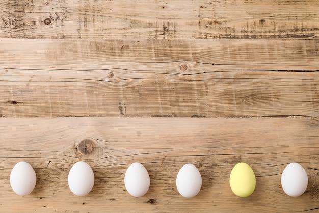 木の背景に白と1つの黄色の卵の上面図