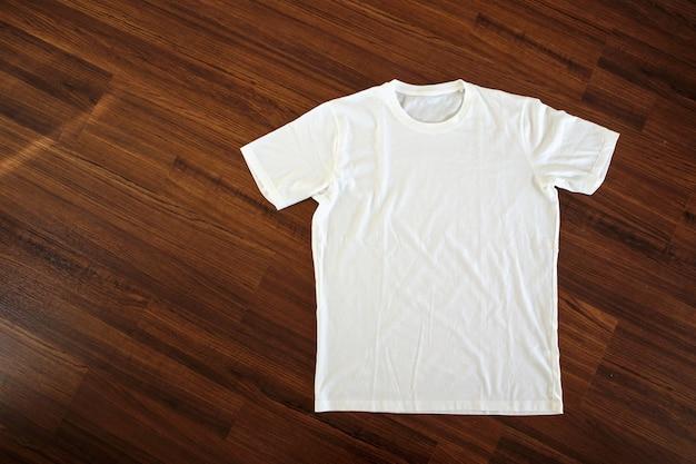 Вид сверху на белую футболку на деревянном фоне