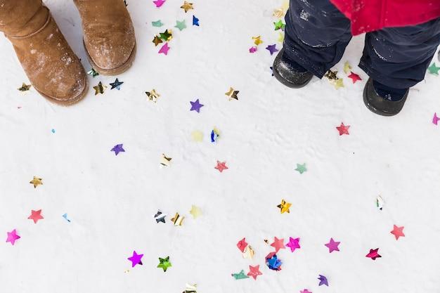 紙吹雪と雪の地面に女性と子供の足の上面図