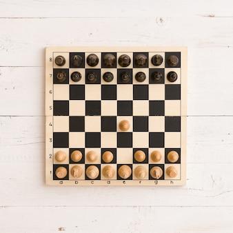 흰색 나무 테이블 배경에 수치가 있는 나무 체스 보드의 상위 뷰