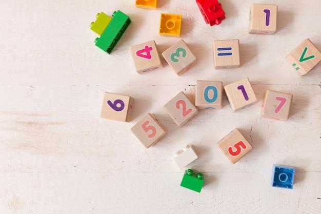흰색 나무 테이블 배경에 숫자와 다채로운 플라스틱 벽돌이 있는 나무 큐브의 상위 뷰