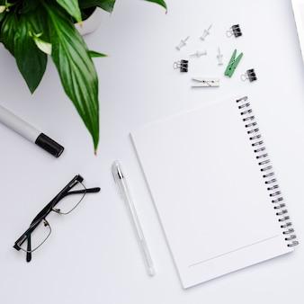 Вид сверху на рабочее пространство с белой записной книжкой со свободным пространством для текста в центре