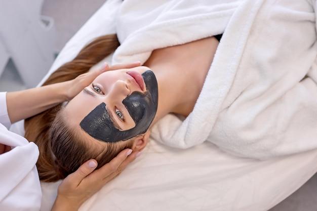 젊은 여성에 대한 상위 뷰는 스파에서 전문 미용사의 서비스를 사용합니다. 잘려진 알아볼 수 없는 마스터 미용사는 고객의 얼굴에 검은 마스크를 씌우고 마사지를 제공합니다. 건강과 장수