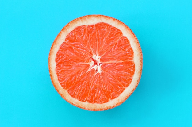 Top view of an one grapefruit slice on bright background in blue color.