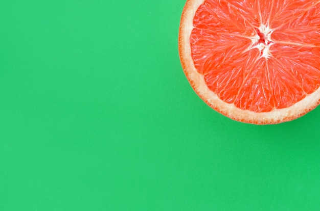 Top view of an one grapefruit slice on bright background in green color