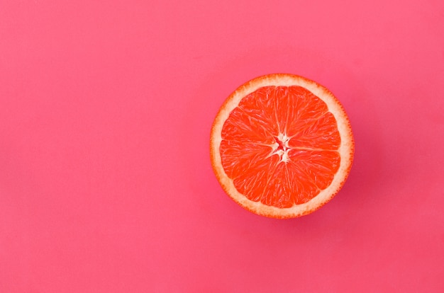 Top view of a one grapefruit slice on bright background in light pink color.