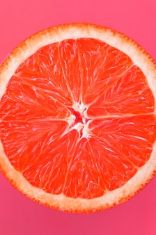 Top view of a one grapefruit slice on bright background in light pink color