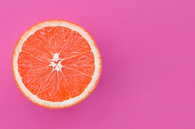 Top view of an one grapefruit slice on bright background in purple color