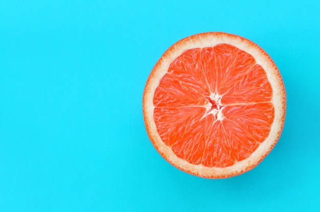 Top view of an one grapefruit slice on bright blue color