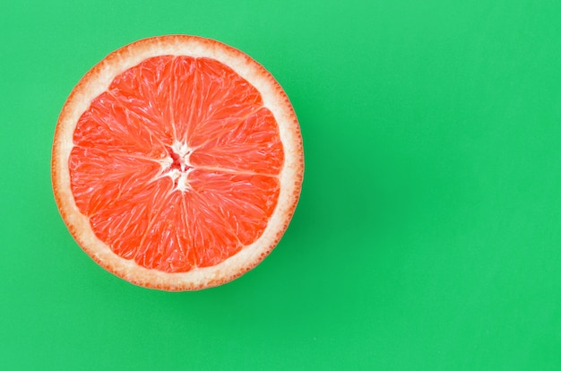 Top view of an one grapefruit slice on bright green
