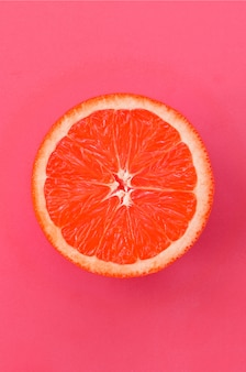 Top view of a one grapefruit slice on bright pink