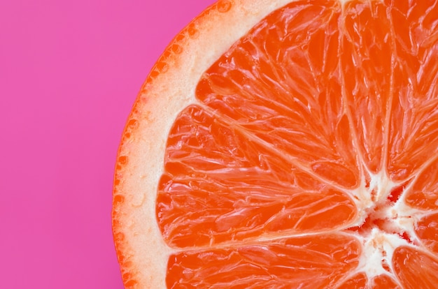 Top view of an one grapefruit slice on bright purple
