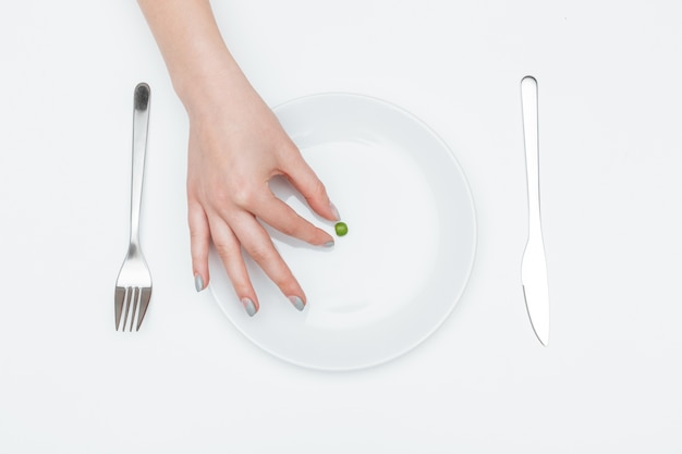 Top view of one green pea on the plate taken by woman hand