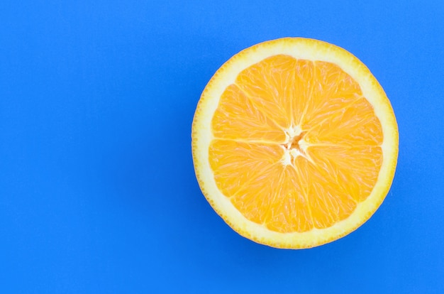 Top view of a one orange fruit slice on bright background in blue color