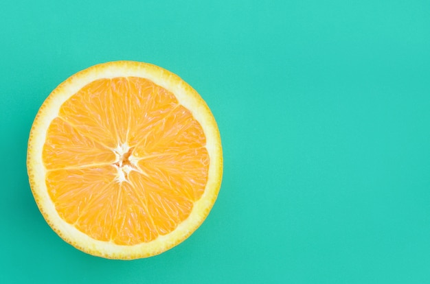Top view of a one orange fruit slice on bright background in turquoise green color