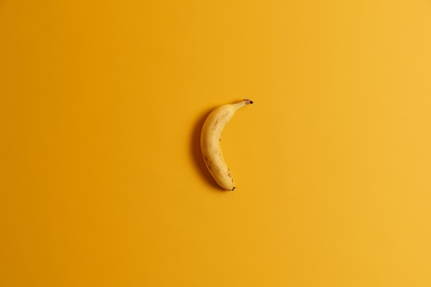 Top view of one ripe banana isolated over yellow background. delicious tropical fruit for your tasty breakfast or snack. ready to eat whole banana. useful nourishing product rich in vitamins
