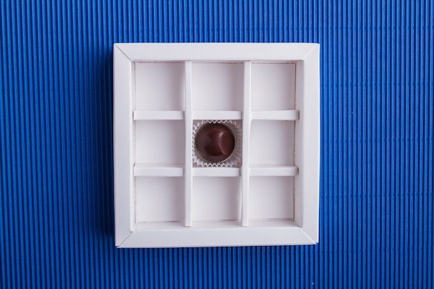 Вид сверху на одну шоколадную конфету в коробке