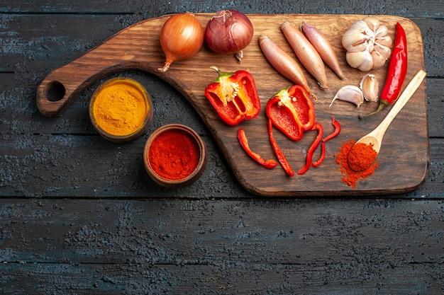 Vista dall'alto di cipolle e aglio con condimenti su scrivania scura cibo pasto insalata piccante pepe