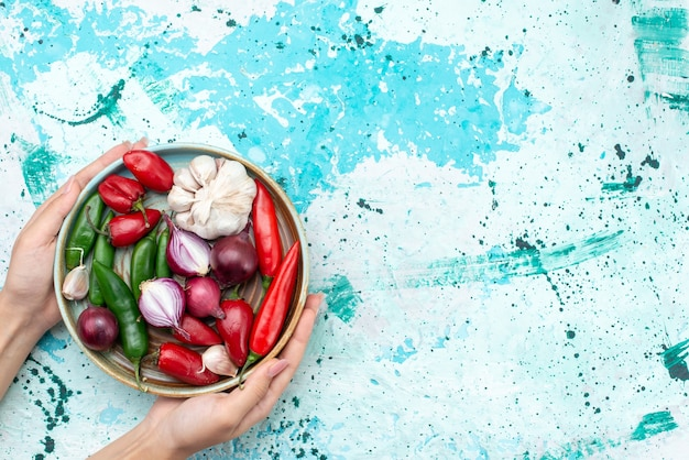 Top view onions and garlics with red chilly peppers inside round plate on the llight-blue background ingredient product food meal vegetable