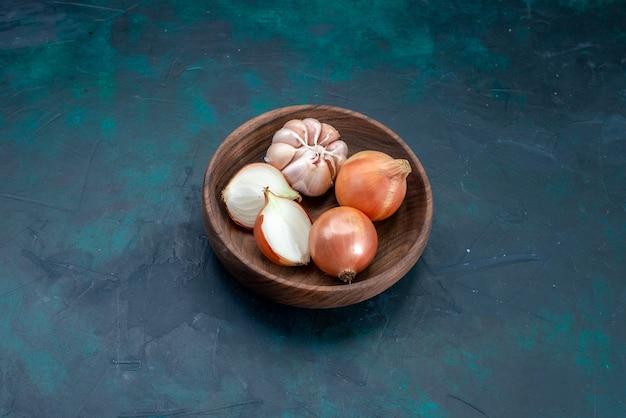 Cipolle vista dall'alto con aglio all'interno della piastra su oscurità
